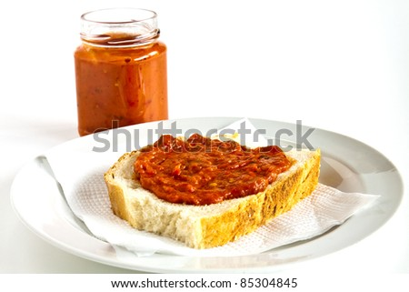 Slice of bread smeared with chutney on white bread - stock photo