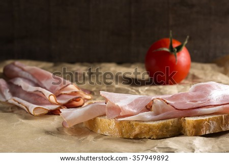 Slice of bread with ham and one tomato over paper background - stock photo