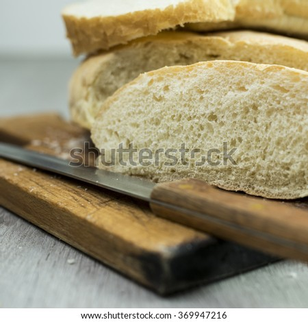 Slice of bread with knife on cutting board - stock photo