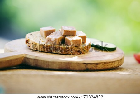 slice of bread with pate on the wooden cutting board