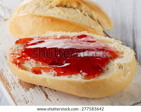 Slice of bread with strawberry jam on a wooden cutting board. Selective focus
