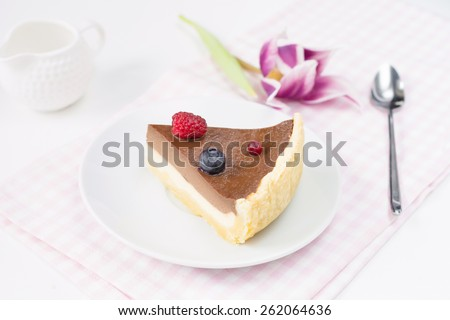 Slice of cheesecake with chocolate layer decorated with blueberry, cranberry and raspberry on white table on pink napkin with single flower on side - stock photo