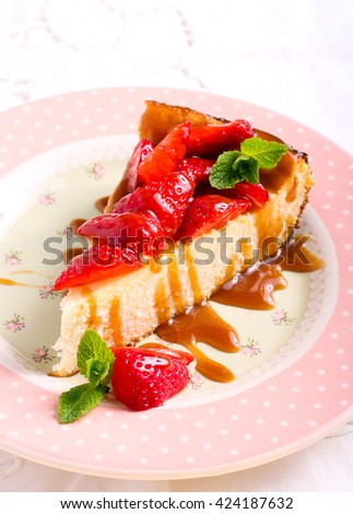 Slice of cheesecake with strawberry and caramel topping
