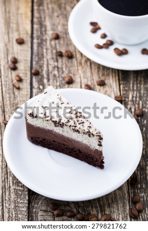 Slice of chocolate cake on the white plate with coffee beans on the wooden background.