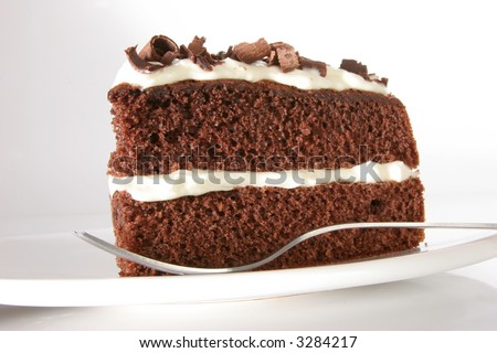 Slice of chocolate cake stuffed with whipped cream, covered with whipped cream and white chocolate on neutral background