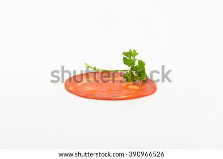 slice of chorizo salami with parslery on white background - stock photo