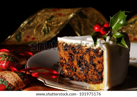 Slice of Christmas cake decorated with holly and berries - stock photo