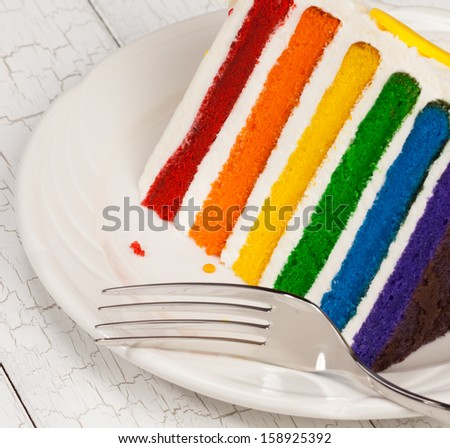Slice of colourful rainbow layered birthday cake decorated with sprinkles and buttercream icing. - stock photo
