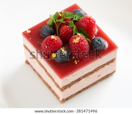 Slice of delicious layered and glazed raspberry mousse cake isolated on white background - stock photo