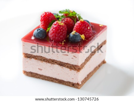Slice of delicious raspberry mousse cake made from layers of chocolate genoise, glazed with raspberry jelly, and decorated with blueberries, raspberries, sprig of chervil, and pieces of gold leaf - stock photo