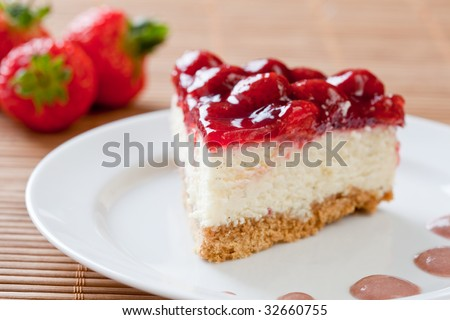 Slice of delicious strawberry cheese cake on a white plate with fresh strawberries in the background