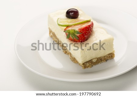 Slice of delicious tangy lemon cheesecake on a biscuit base topped with fresh strawberry and a slice of lemon or lime - stock photo
