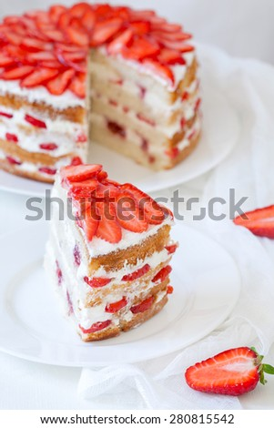 Slice of delicious traditional rustic summer strawberry cake sweet dessert food with whipped cream and red fresh strawberries on white kitchen table background. Rustic style, natural light. - stock photo