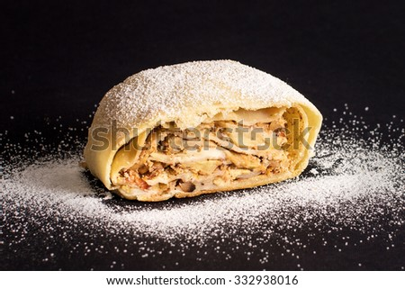Slice of fresh baked homemade apple strudel with walnut and sugar powder, isolated on a black background - stock photo