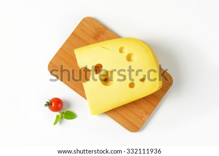 slice of fresh cheese on wooden cutting board - stock photo