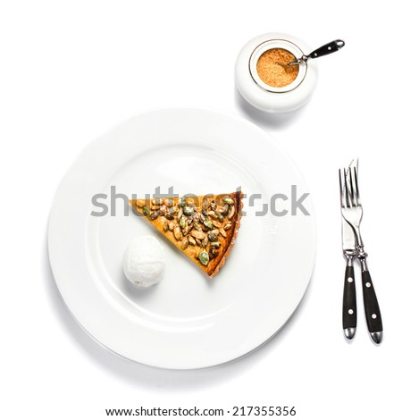 Slice of fresh Pumpkin Pie with whipped cream and pumpkin seeds on white plate isolated on white background - stock photo
