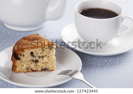 Slice of fruitcake made with raisins and cup of tea