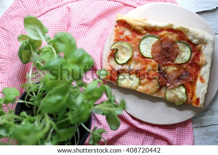 Slice of homemade pizza with tomato sauce, zucchini, spicy salami, mozzarella and basil leaves. On white rustic table, decorated with checkered tablecloth and basil pot. Top view, selective focus. - stock photo
