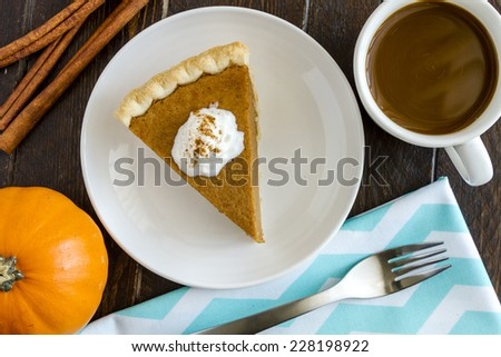 Slice of homemade pumpkin pie with whipped cream sitting on white plate next to cup of coffee with small pumpkin, cinnamon sticks and fork on blue chevron napkin - stock photo