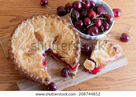 Slice of hot cherry pie removed from the whole garnished with red ripe cherries. - stock photo