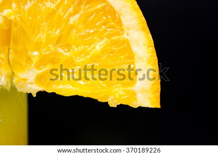 Slice of juicy orange ripe vitamins orange  close-up, on the black background - stock photo