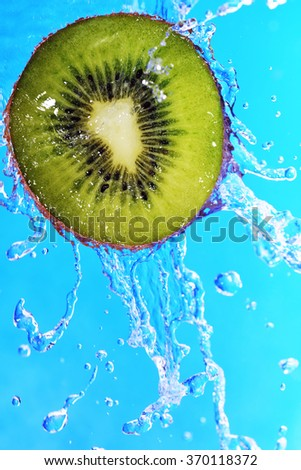slice of kiwi in the water with bubbles on blue background - stock photo