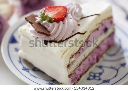 slice of layered cake with berry mousse and with chocolate icing - stock photo