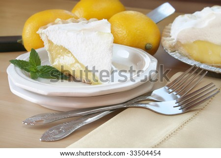 Slice of lemon meringue pie garnished with mint leaves. - stock photo