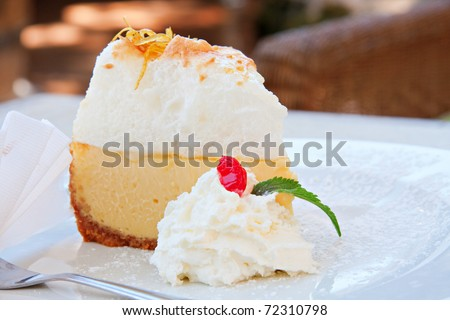 slice of lemon meringue pie on white plate with cream - stock photo