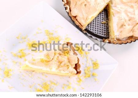 Slice of Lemon Meringue Tart on a plate decorated with lemon peel - stock photo