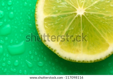 Slice of lime with drop on green background - stock photo