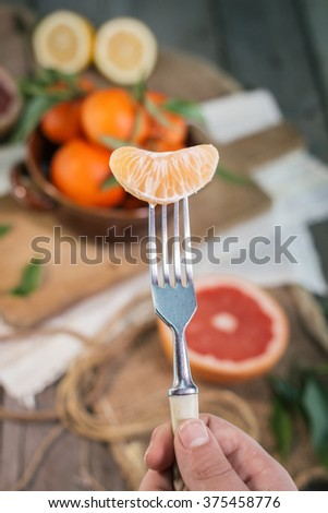 Slice of mandarin on fork - stock photo