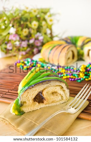 Slice of Mardi Gras King Cake - Slice of traditional New Orleans style King Cake to celebrate Mardi Gras. It's decorated in the traditional Mardi Gras colors of purple, gold, and green with beads. - stock photo