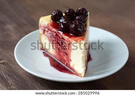 Slice of New York cheesecake topped with cherry compote on plate, brown wooden table background - stock photo