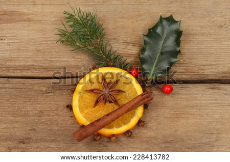 Slice of orange with cloves, star anise,cinnamon and seasonal foliage on weathered wood - stock photo