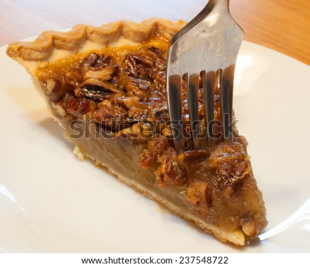 Slice of pecan pie with a fork just going in - stock photo