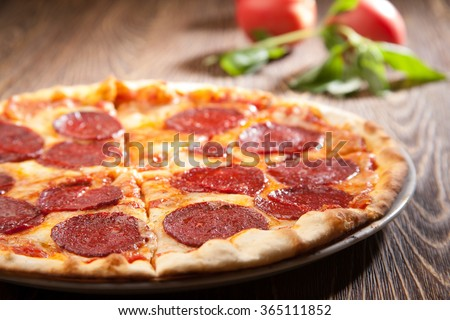 Slice of Pepperoni Pizza being removed from whole pizza with tomatoes in background