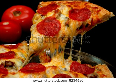 Slice of pepperoni pizza being removed from whole pizza with tomatoes in background.  Isolated on black background. - stock photo