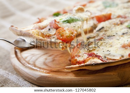 Slice of pizza with ham, vegetables and cheese taken from wooden pizza peel with steel pizza slice server - stock photo