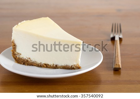 Slice of Plain New York Cheesecake on white plate on wooden background - stock photo