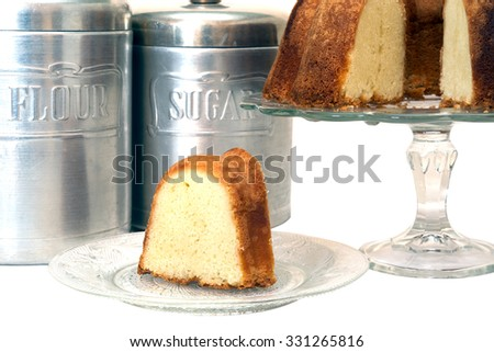 Slice of pound cake removed from whole cake which is in background along with flour and sugar canisters.  Isolated on white background with clipping path.