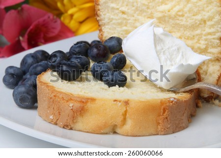 Slice of pound cake with whipped cream topped and blueberries with flowers in the background - stock photo