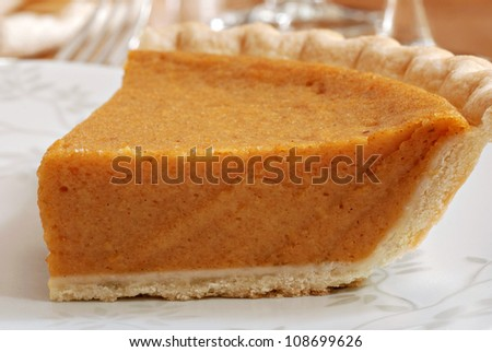Slice of pumpkin pie on decorative plate with dinnerware in background.  Macro with shallow dof.