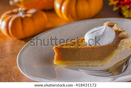 Slice of Pumpkin Pie on Dessert Plate with Whipped Cream and Pumpkins in Background