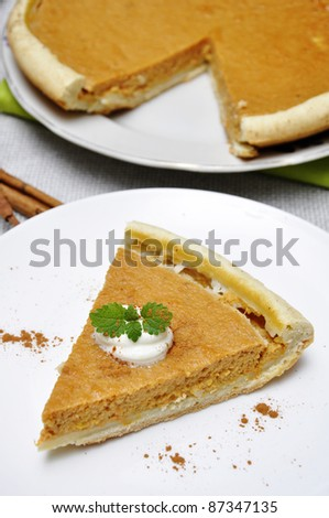 Slice of pumpkin pie with whipped cream and mint served on white plate