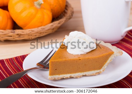 Slice of pumpkin pie with whipped topping - stock photo