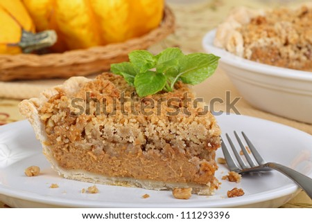 Slice of pumpkin streusel pie with mint leaves on a plate - stock photo