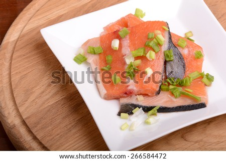 Slice of red fish salmon on white plate - stock photo