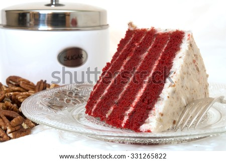 Slice of red velvet cake closeup with sliced pecans and sugar canister in background.  Cake is on plate along with fork.  Isolated on white background. - stock photo