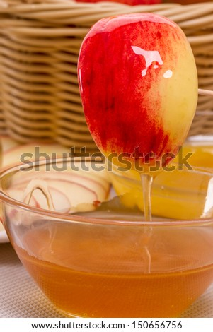 Slice of ripe apple with honey flowing down - stock photo
